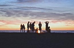 People enjoying a Cascadian Summer bonfire as the sun sets.